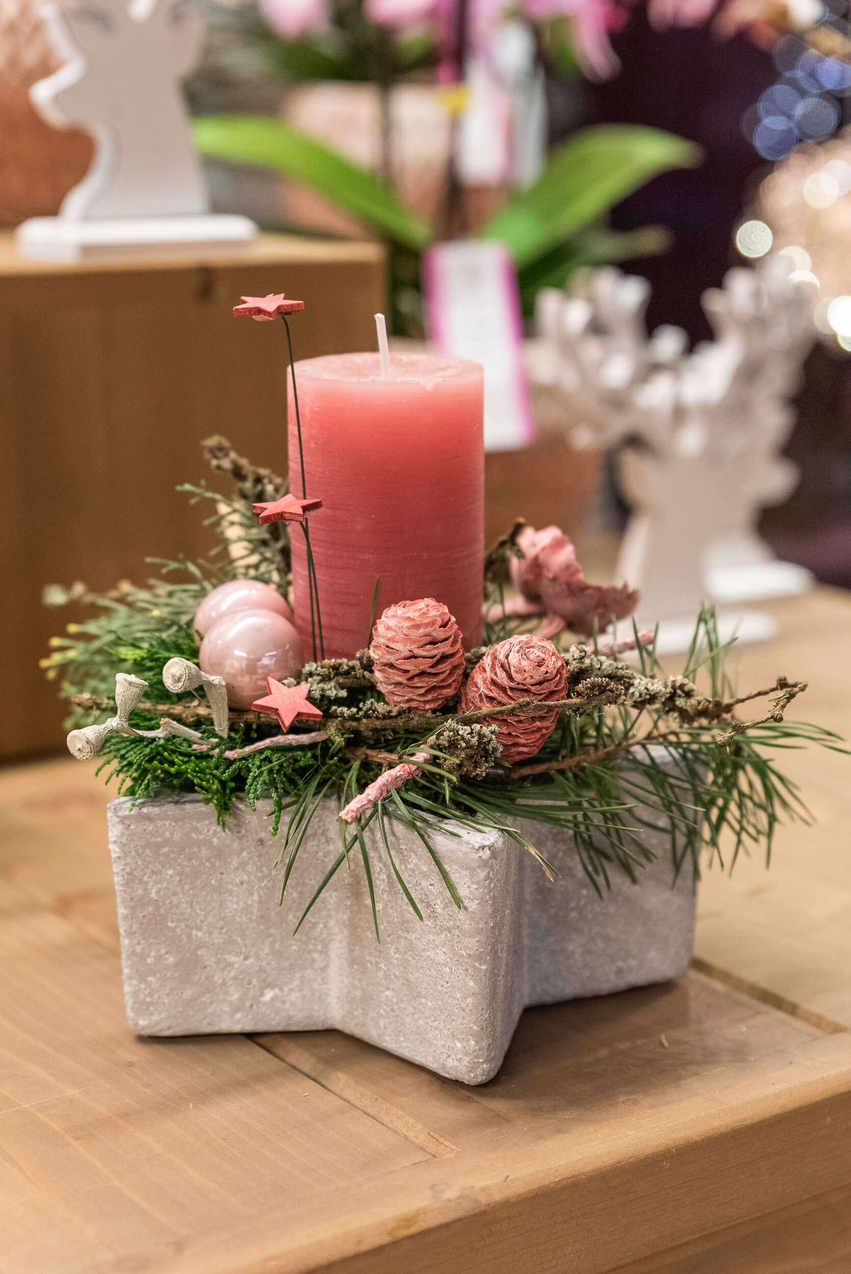 Adventsgesteck mit korallfarbener Kerze