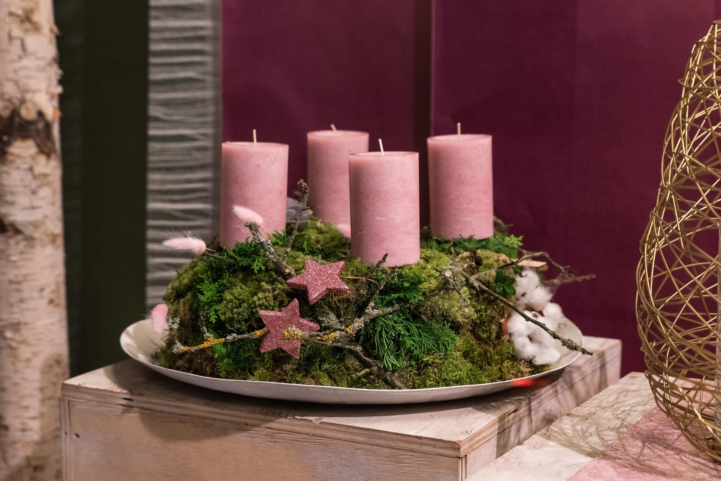 Adventskranz auf Teller mit rosanen Kerzen