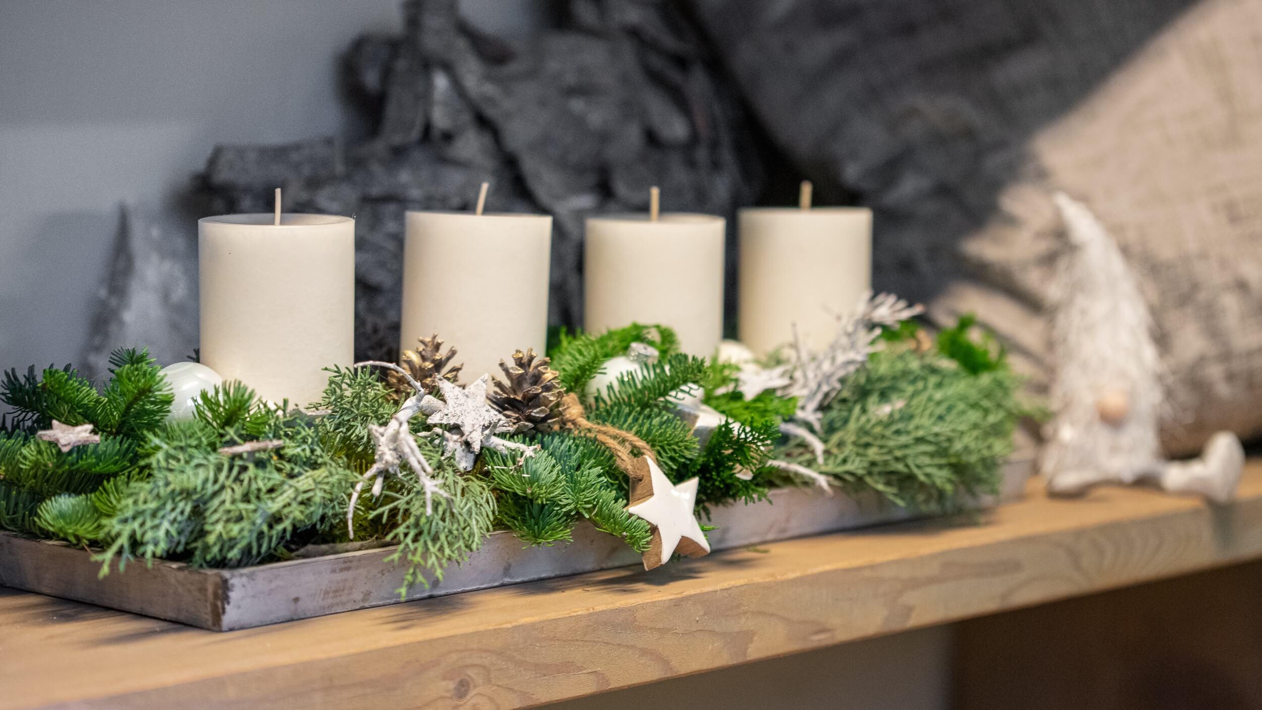 Weißes Adventsgesteck mit Zapfen